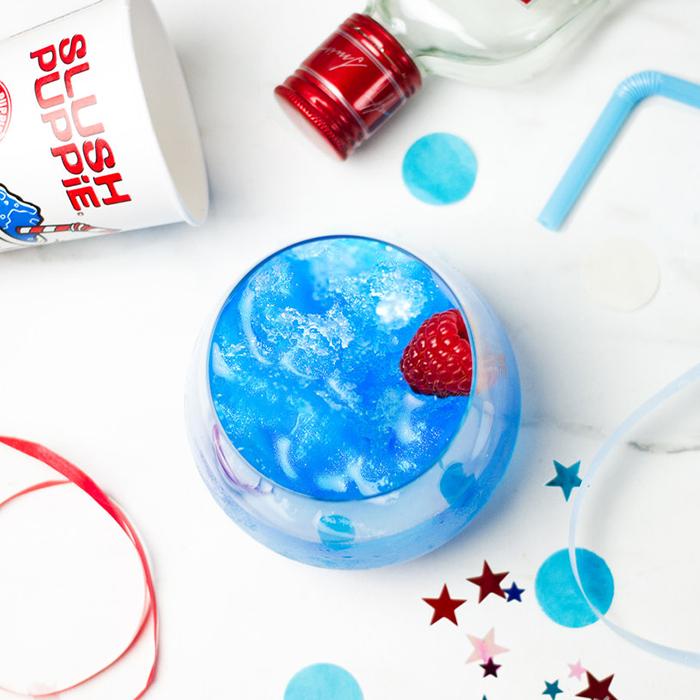 Blue Slush Puppie with red raspberry as garnish