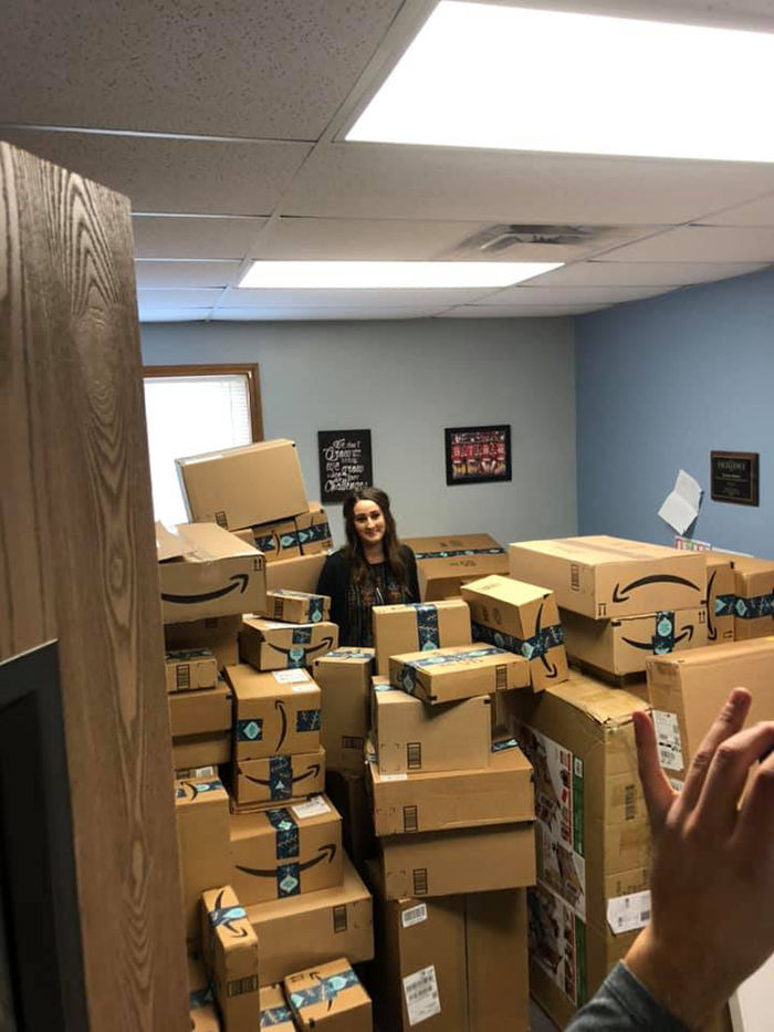 Boxes of gifts from Kristen Bell fan fill the classroom