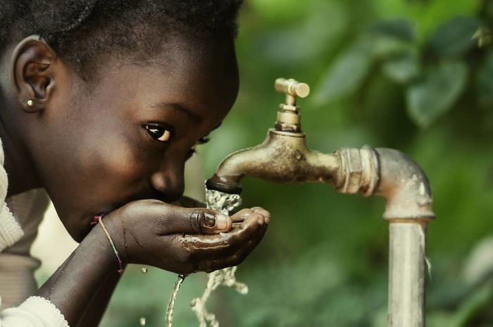 Kenyan Girl Drinking Water from a Faucet