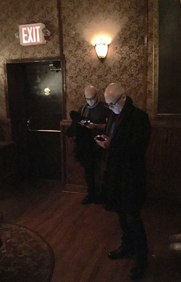 bald guys with eyeglasses checking out phone