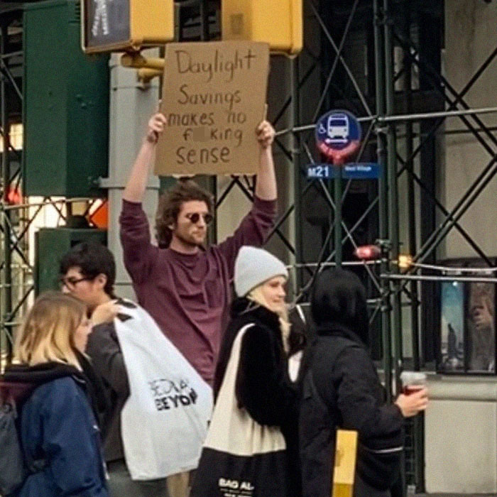 dude with sign daylight saving