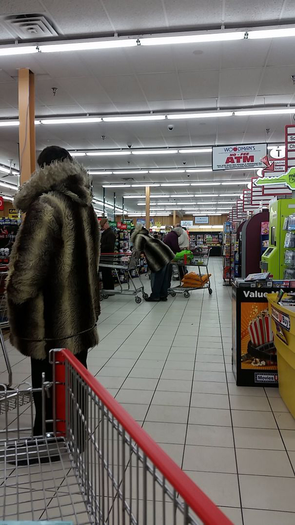 two people wearing striped fur coats at a supermarket
