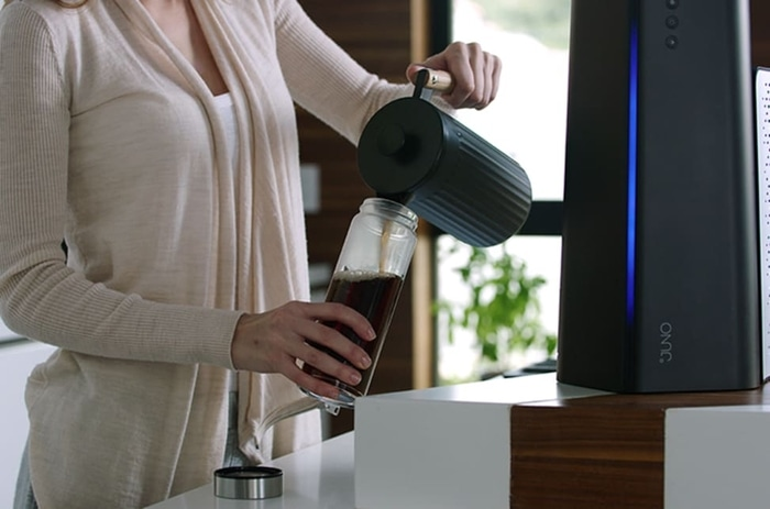 Lady Pouring Freshly Brewed Coffee into a Tumbler