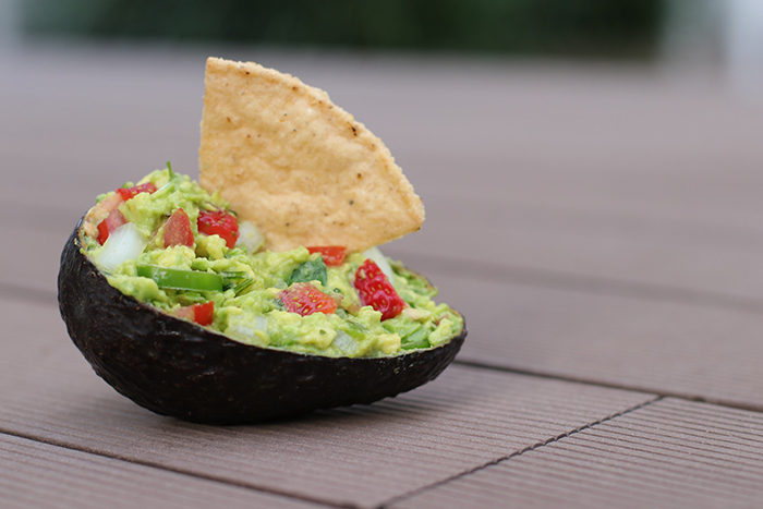 a chip dipped in mashed avocado dip