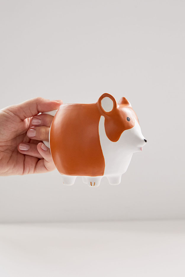 model holds the corgi dishware mug