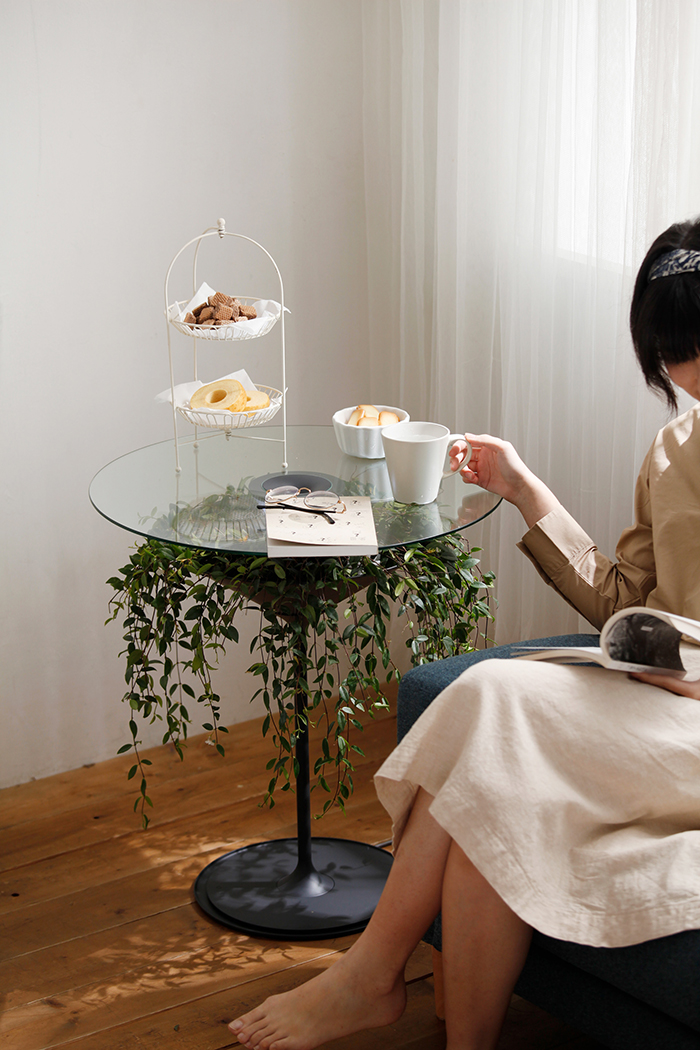 pei-ju wu enjoys tea while reading a book beside her glass table