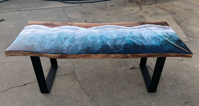 wooden table with crashing wave resin design and flat iron legs