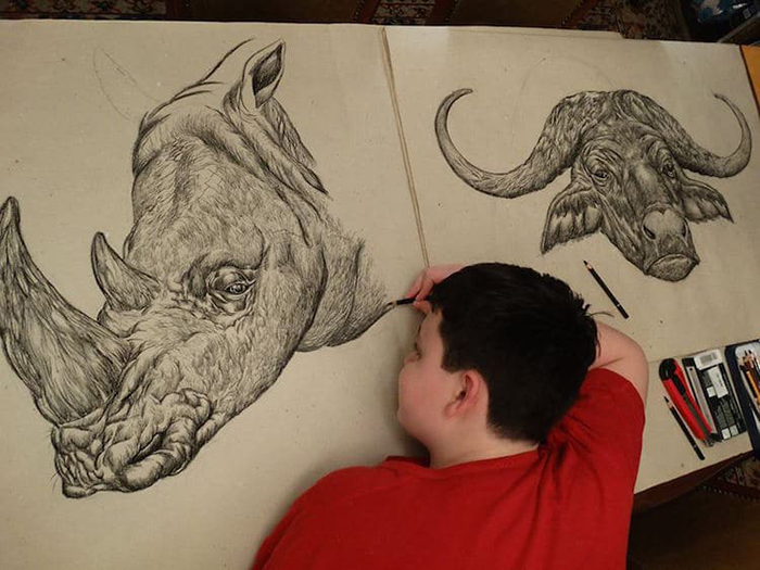 Dusan lays on the floor to make his animal drawings