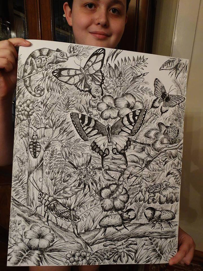 Dusan shows off his drawing of butterflies, beetles and chameleons