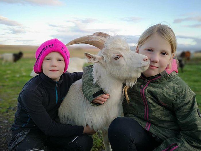 children with a white goat