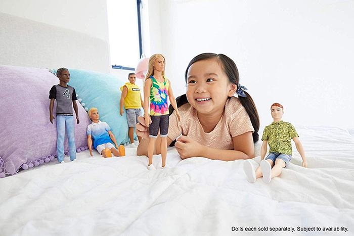 little girl plays with Fashionista Ken dolls