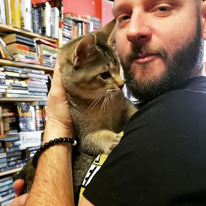 man cradles a kitten in the bookstore