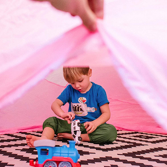 Boy Playing with Toy Cars Inside Inflatable Play Tent