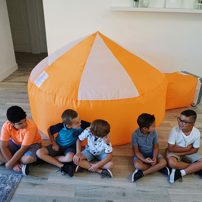 Boys Sitting Outside an Inflatable Play Tent