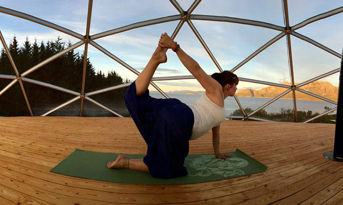 Ingrid does yoga on their cob house's deck
