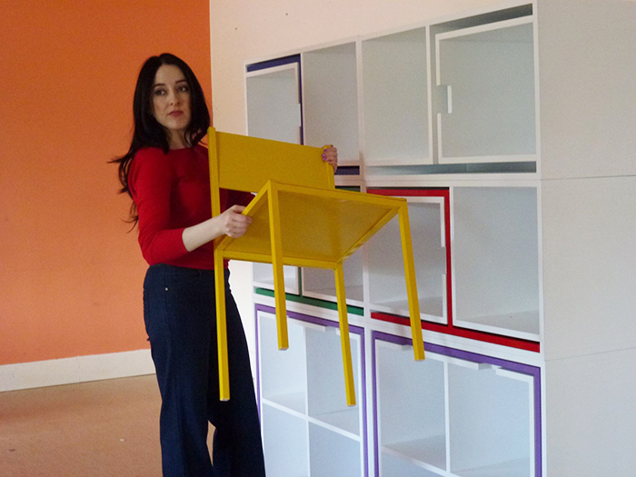 Orla Reynolds Carrying a Yellow Chair