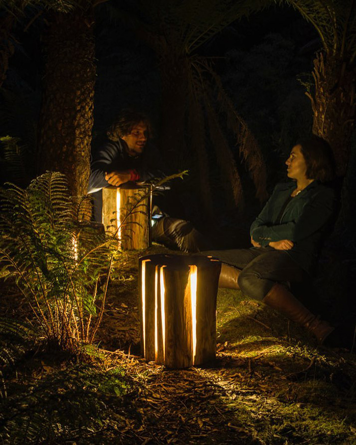 Two Persons in the Forest Using Log Lamps as Light Source