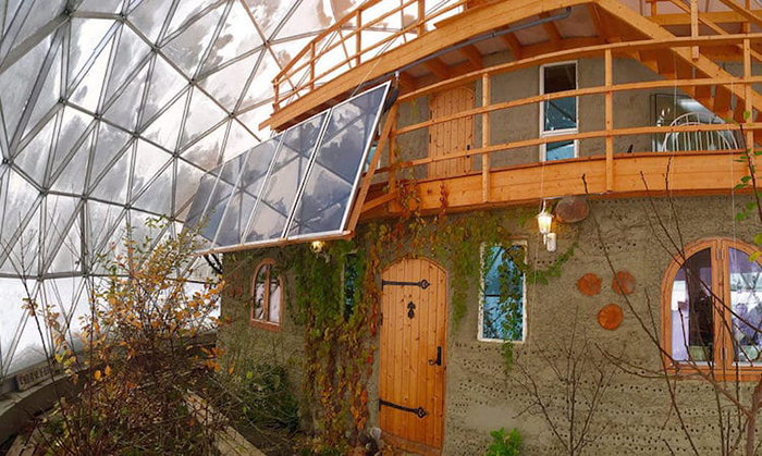 cob house garden with solar panels under the dome