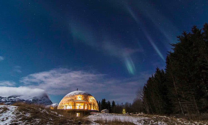 lighted cob house with northern lights