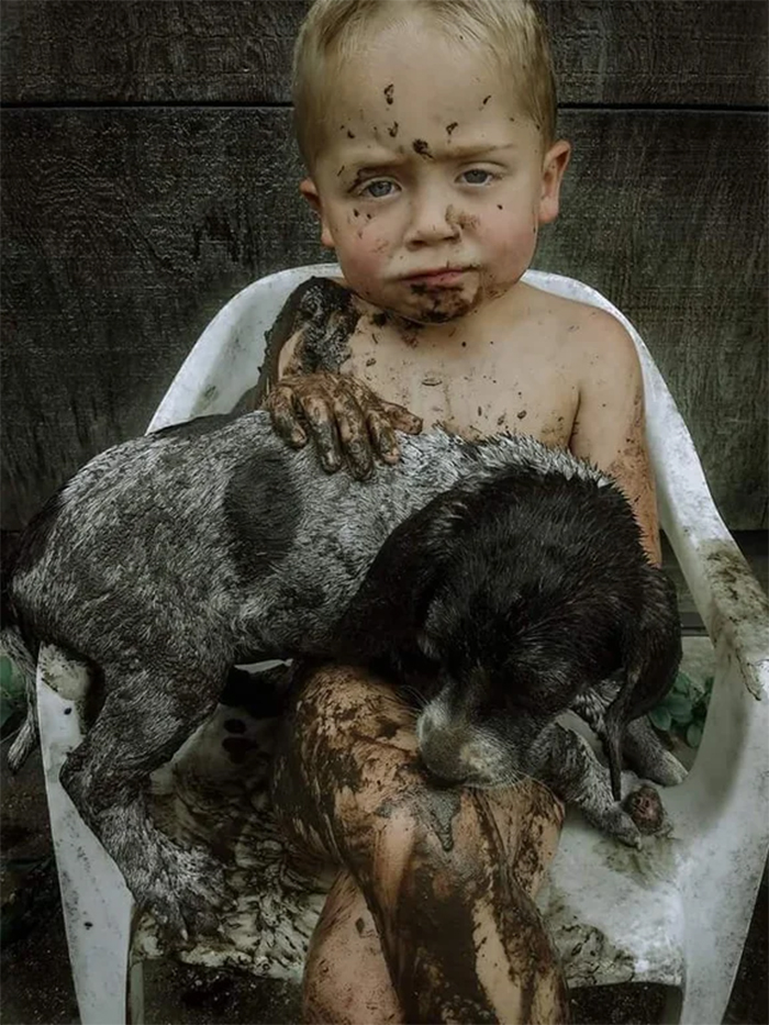 little boy and puppy mud playmates