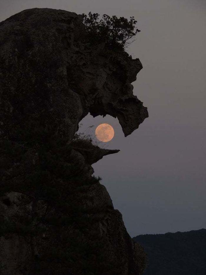 rock formation looks like it's swallowing the moon
