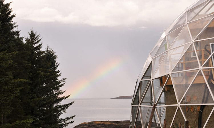 the geodesic dome-protected cob house with an overlooking view