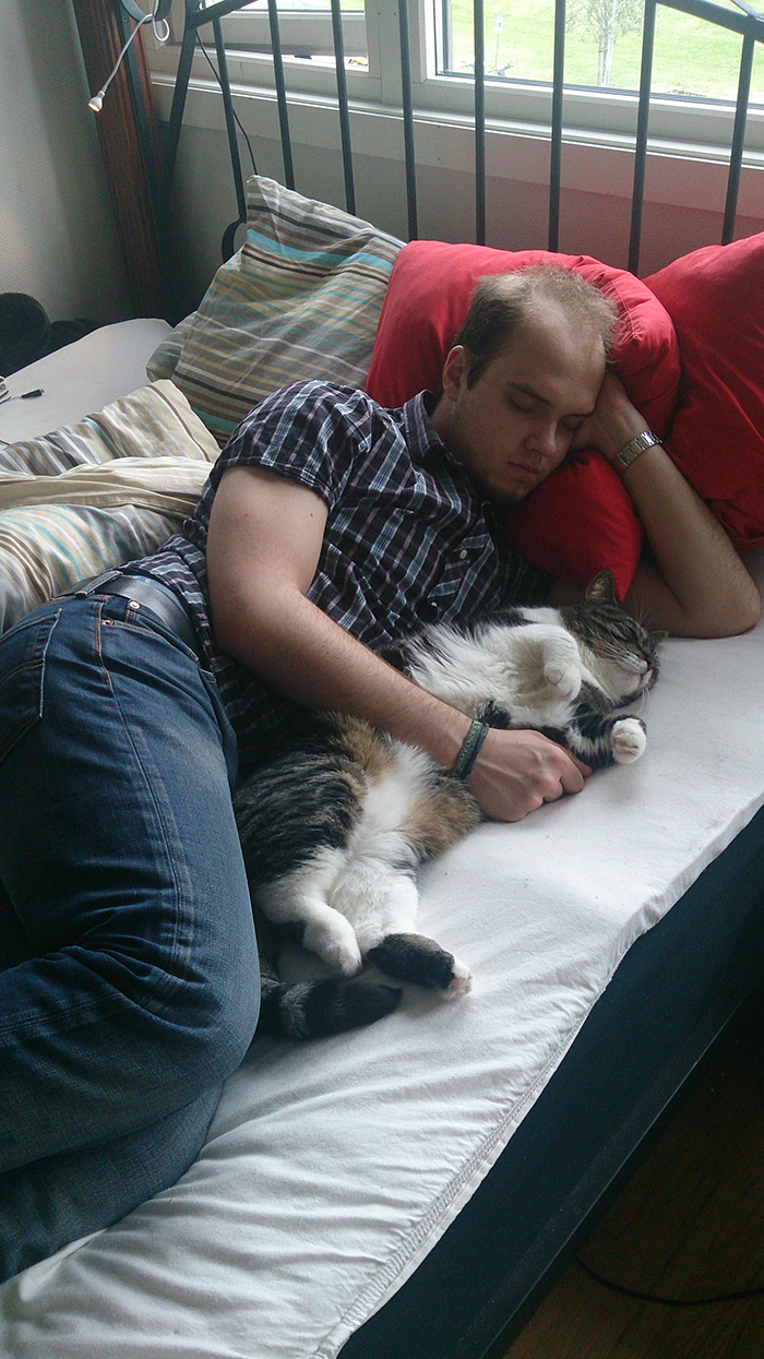 Man Holding Cat while Sleeping