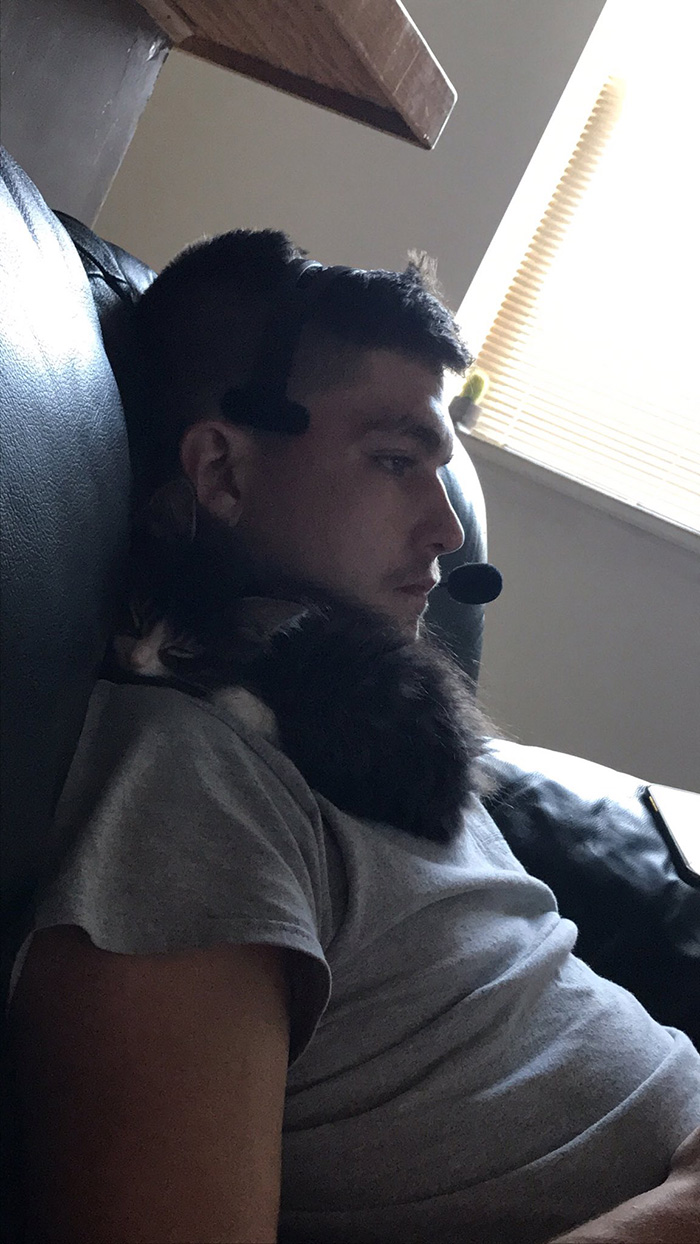 Man Sitting on Couch with Black Kitten on Shoulder