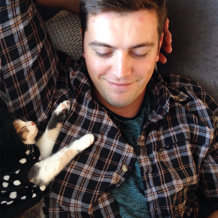 People Who Didn't Want Cats Boyfriend Lying on Couch with Cat