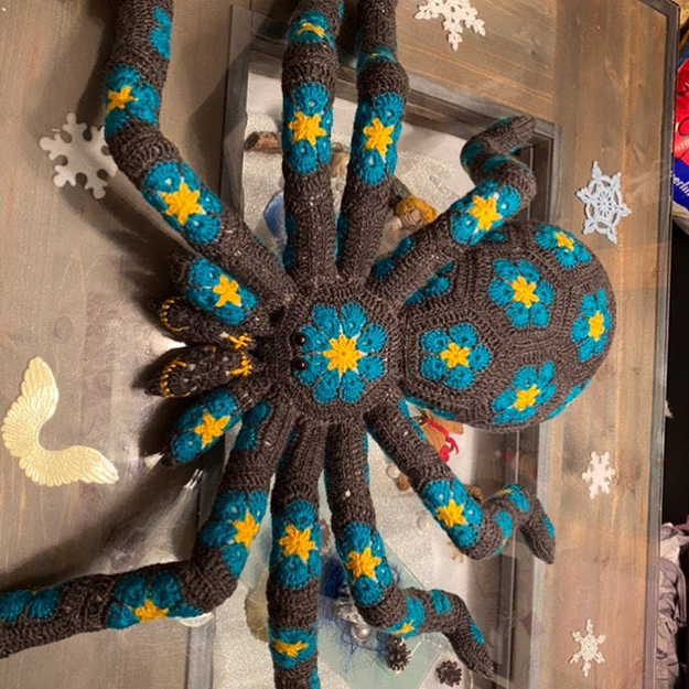 dark gray crochet spider with yellow and blue flower deails