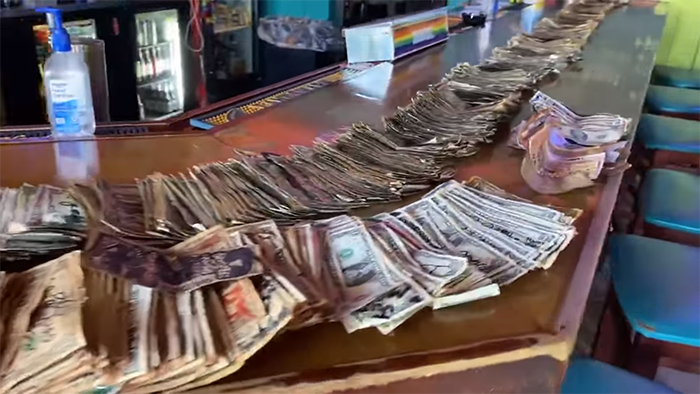 dollar bills removed by bar owner lined up on bar counter