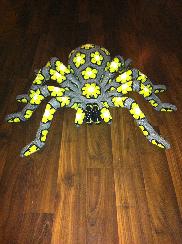 gray giant crochet spider with bright yellow flowers