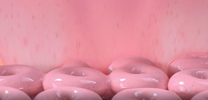 krispy kreme doughnuts passing under strawberry glaze waterfall