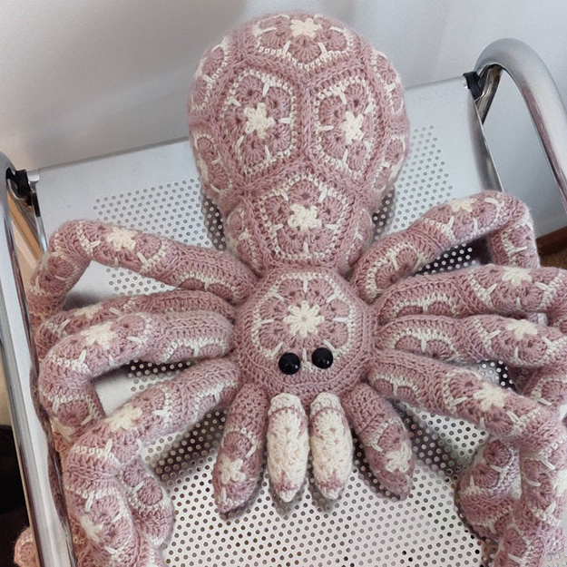 pink giant crochet spider on a metal chair