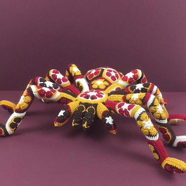 yellow giant crochet spider with a variety of colors in the details
