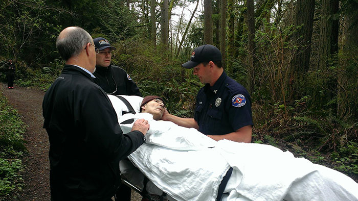 firefighters roll former forest ranger through the woods