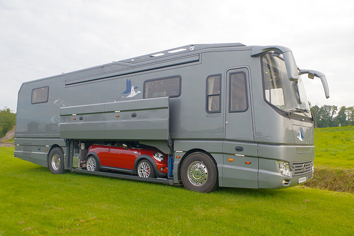gray luxury motorhome with mini cooper in the built-in garage