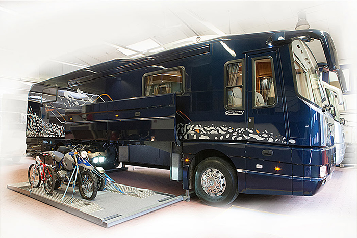 navy luxury motorhome with bikes in the built-in garage platform