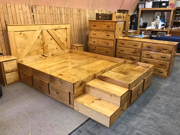 wooden king bed with dog bed extension and dressers in golden oak finish