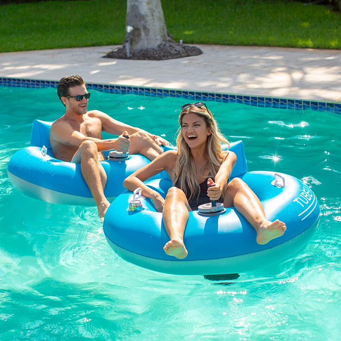 Man and Woman Sitting on Motorized Pool Tubes
