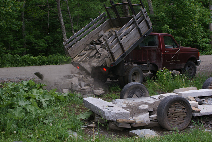 chris miller builds truck sculpture out of rocks