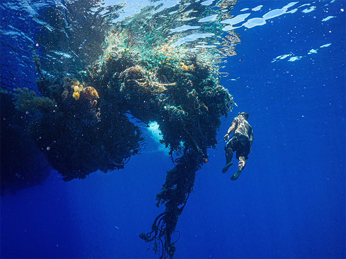 diver next to a large mass of ocean plastic