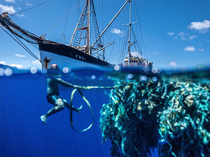 diver pulls a mass of ocean plastic