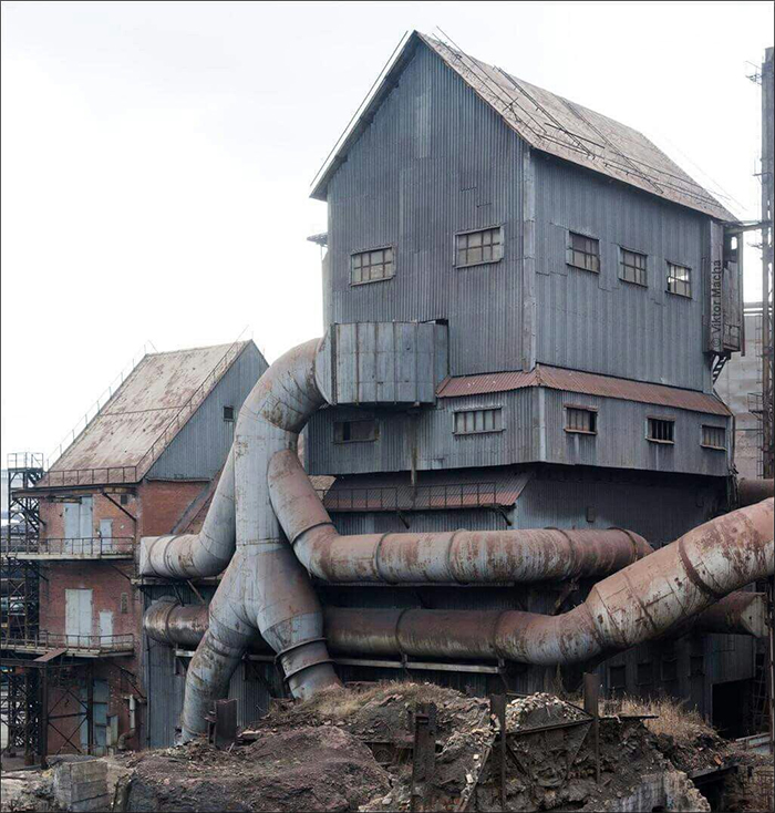 giant tin man checking a building