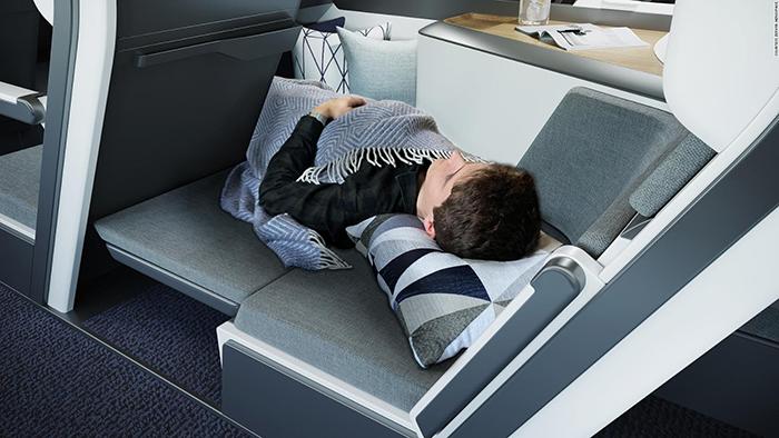 man sleeping on plane seat economy class