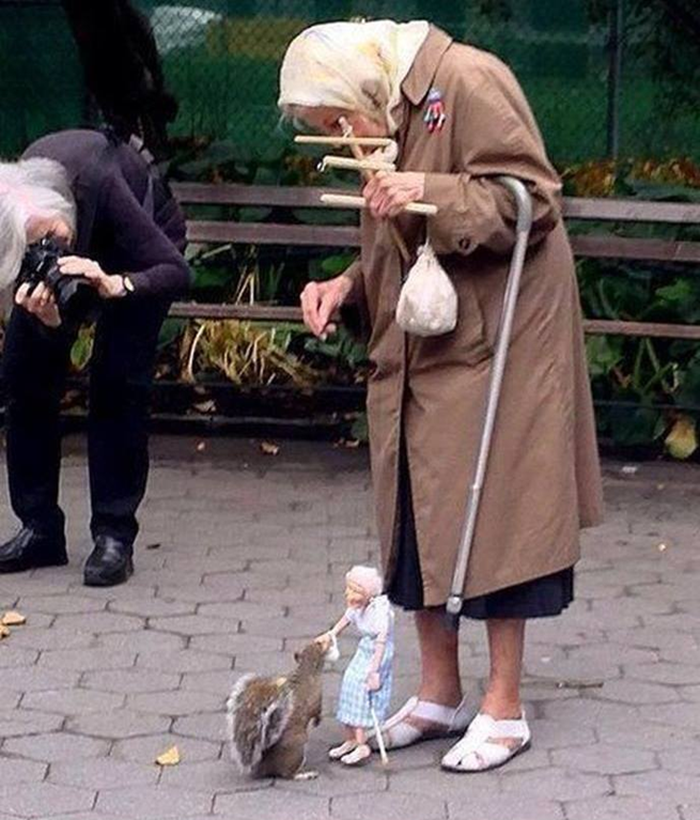 old woman using marionette to feed squirrels
