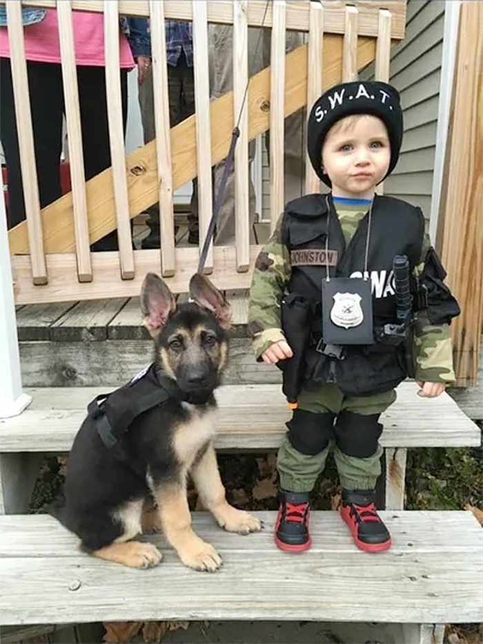 child and dog dressed as swat members