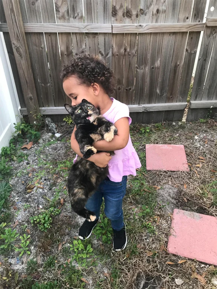 girl holding a scared kitty