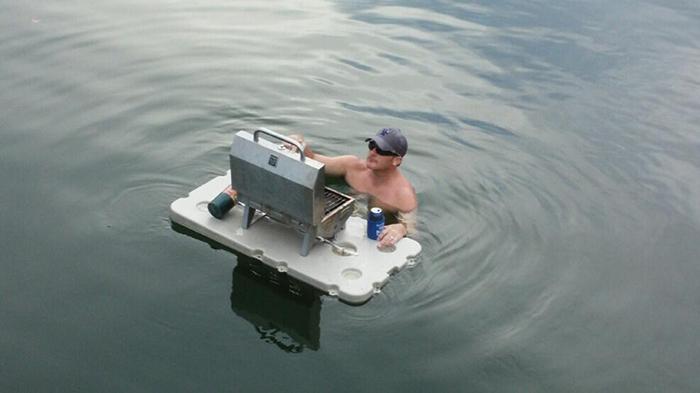 man with a bbq grill on floating bar