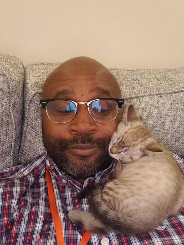 wholesome cat posts cat sleeping on a man's shoulder